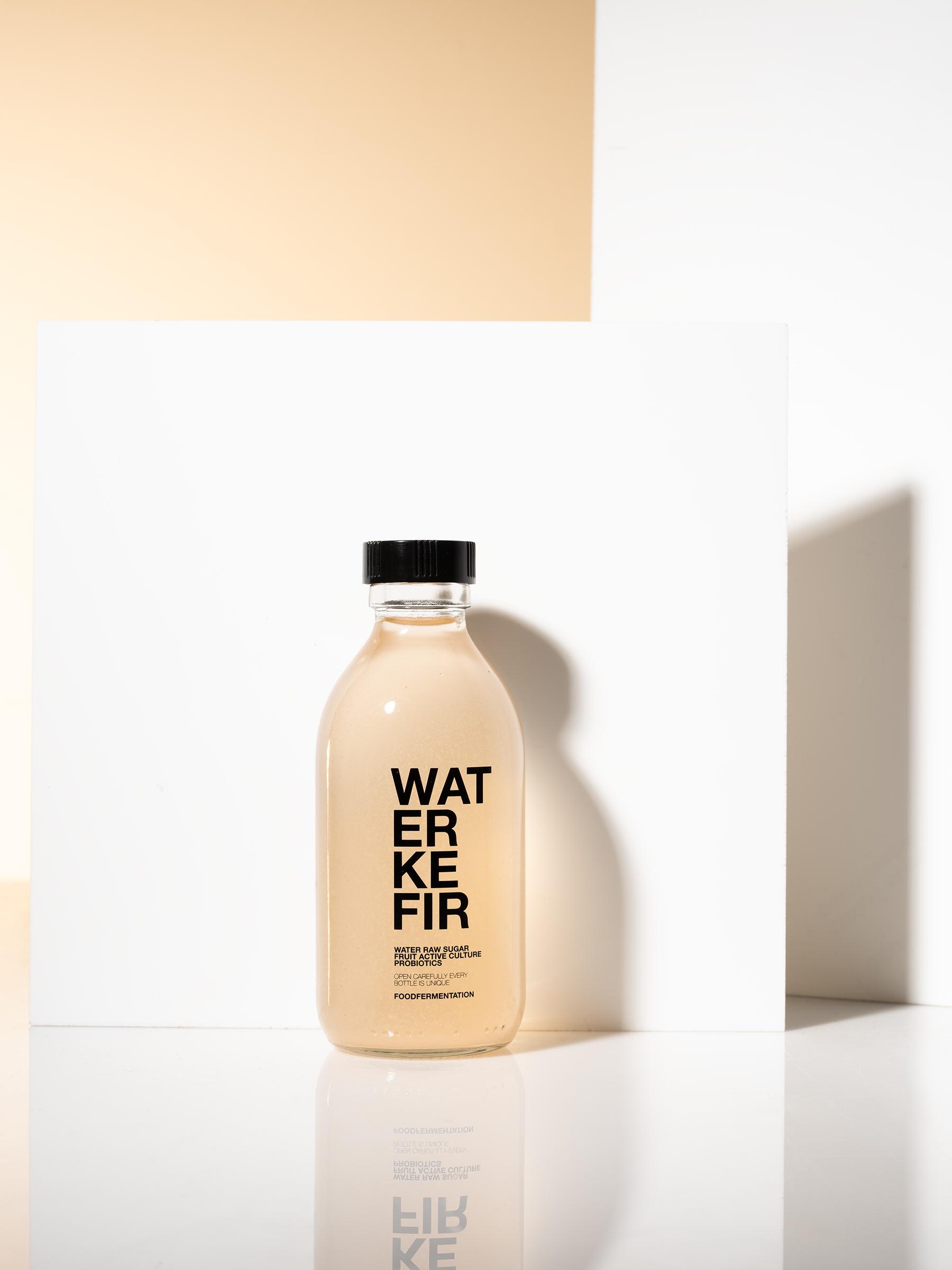 Water kefir flaska fotograferad i studio med skuggspel