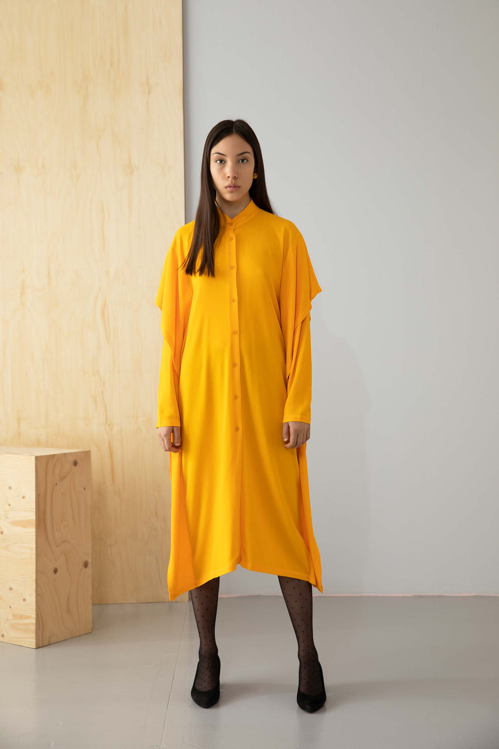 Modell i gul klänning fotograferad i studio
