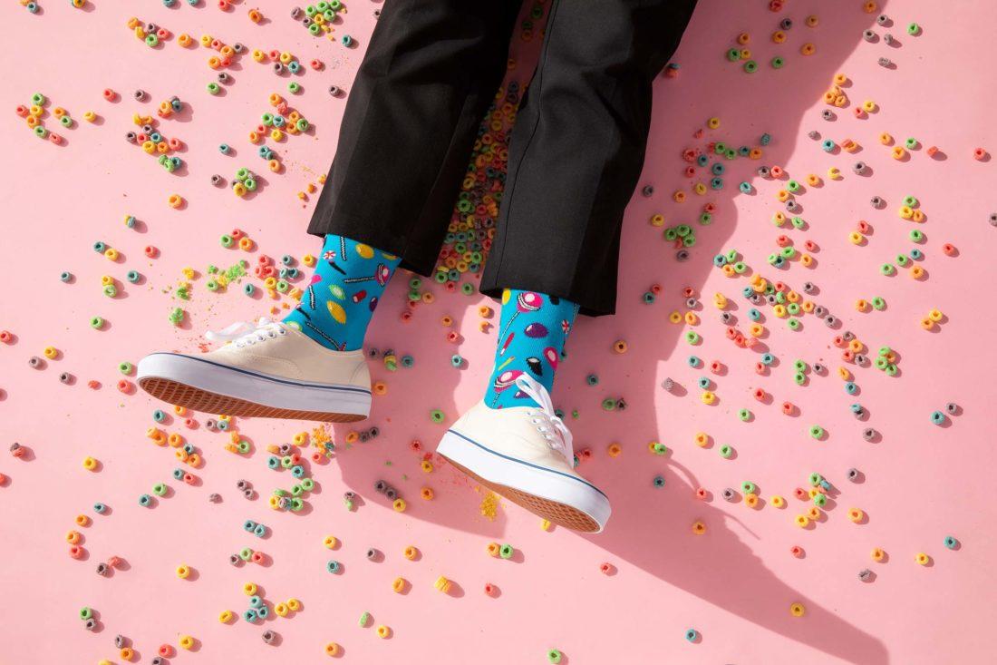 Ben med färgglada Happy socks på rosa golv med flingor