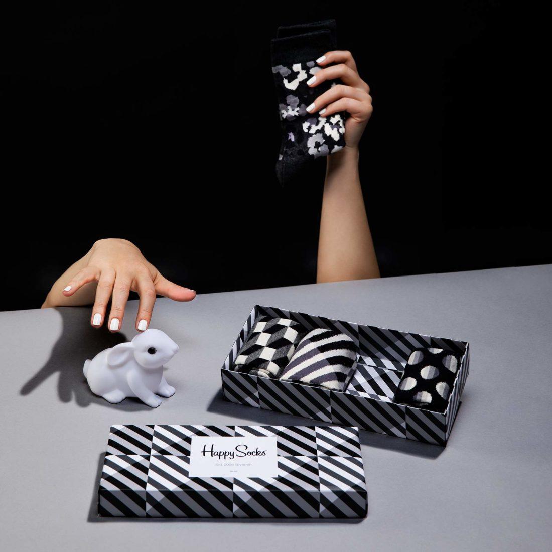 Svartvit Happy socks presentbox och en hand som klappar en kanin