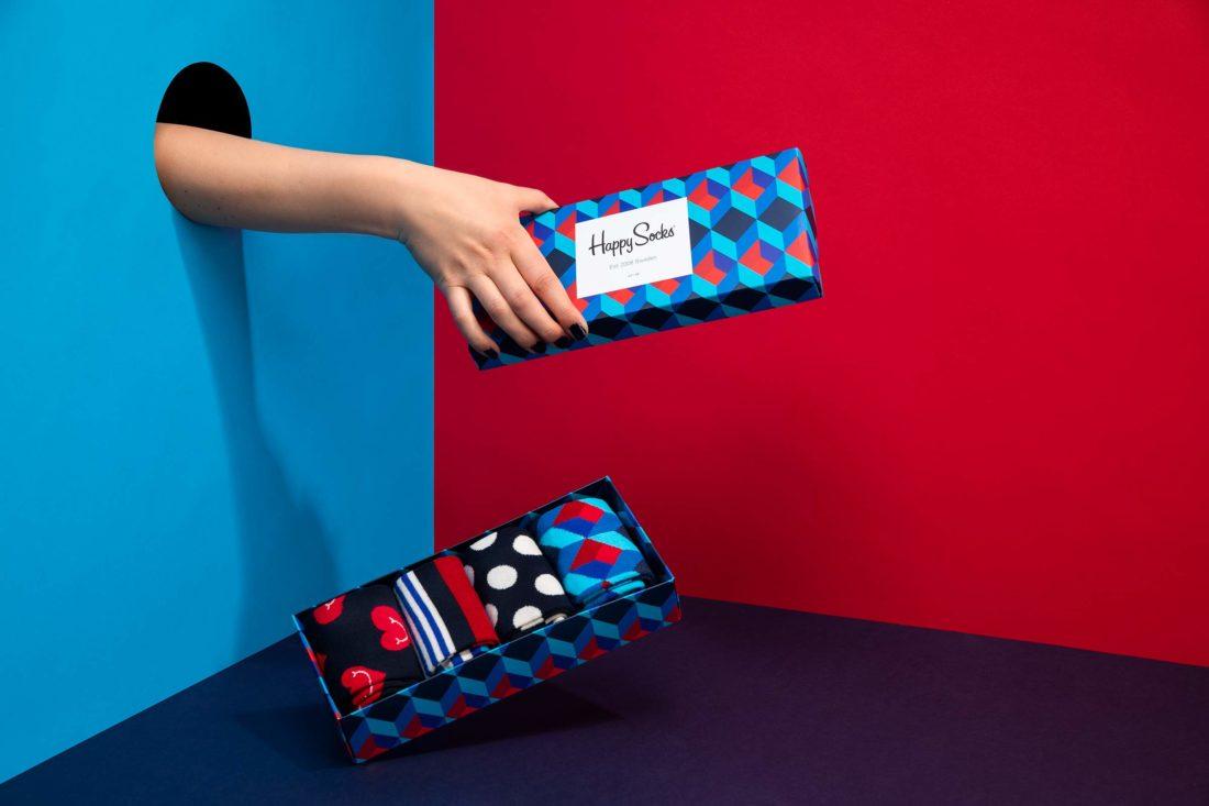 Hand som tappar en låda med strumpor från Happy socks