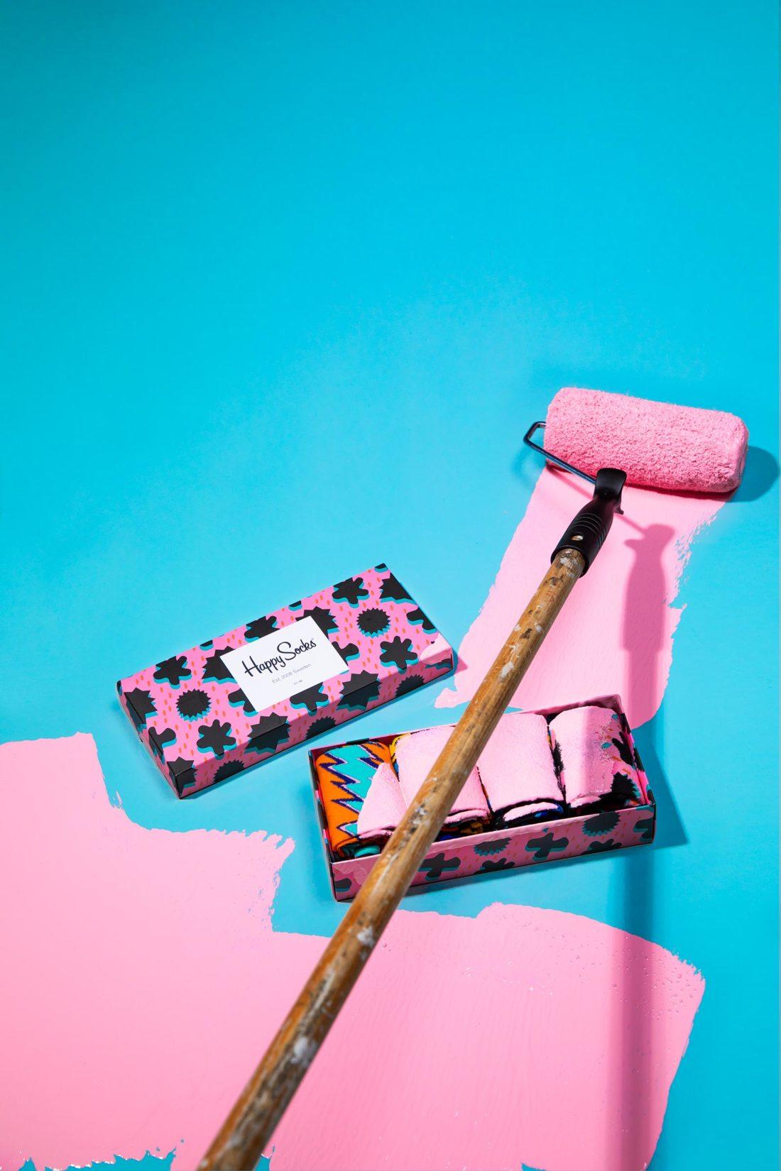 Roller med rosa färg som målar över en Happy socks strumpbox