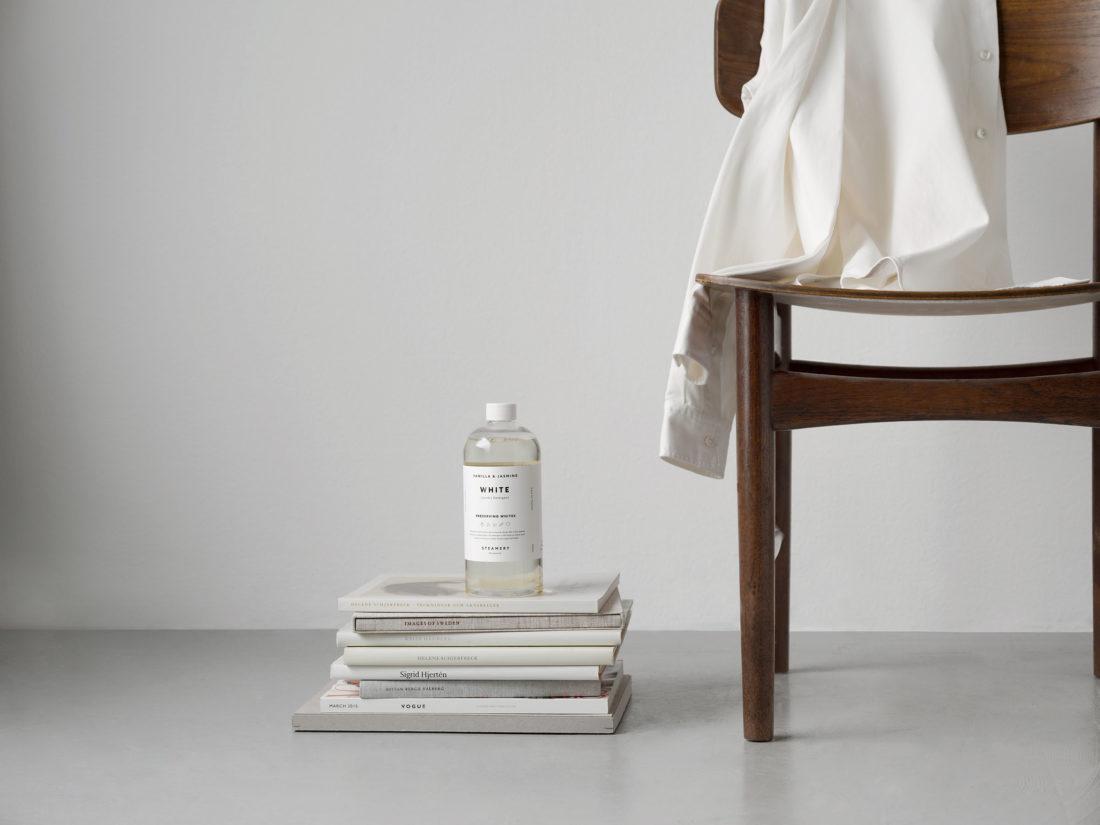 Interiör bild på tvättmedelsflaska på tidningshög fotograferad för Steamery