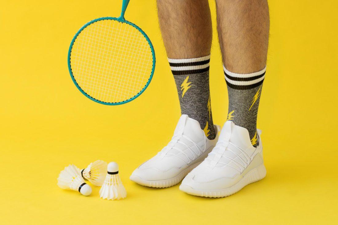 Badmintonrack och badmintonbollar intill ett par ben med blixtstrumpor fotograferad för Happy socks