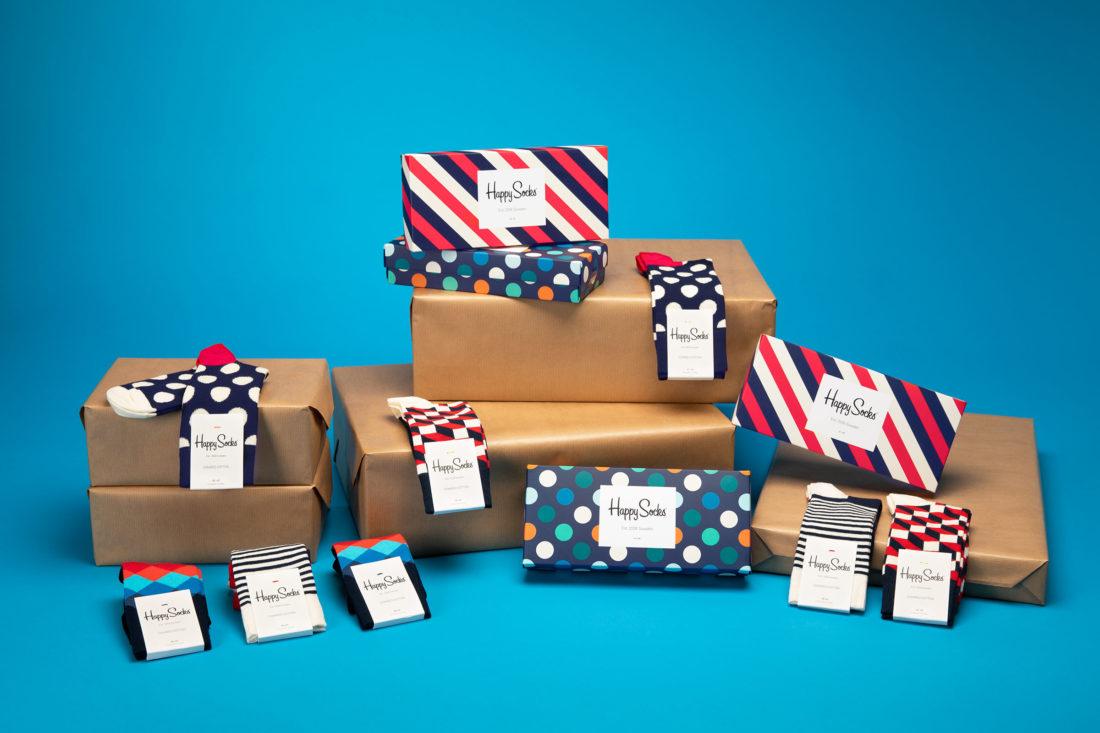 Berg av strumpor och gåvoboxar fotograferad för Happy socks